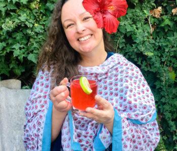 Hibiscus tea with fresh flower petals girl holding tea